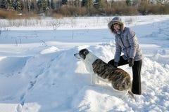 妇女使用与一条狗在冬天 免版税库存图片