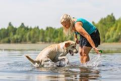 妇女使用与一条狗在湖 库存照片