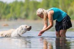 妇女使用与一条狗在湖 库存图片