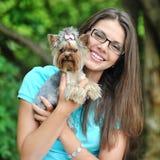 妇女使用与她小的小狗的在一个绿色公园-特写镜头po 图库摄影
