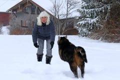 妇女使用与她的在雪的猫 免版税库存照片