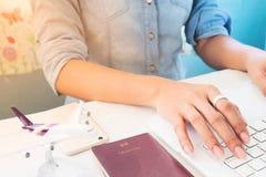 妇女使用便携式计算机、飞机模型和护照的` s手 免版税库存图片
