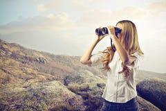 妇女使用双筒望远镜 免版税库存图片