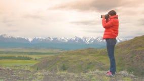 妇女使用户外DSLR照相机的摄影师照相在远足 拍在居住之外的女性徒步旅行者照片室外 股票录像
