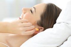 妇女使用插座的覆盖物耳朵在床上 库存照片