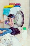 妇女使用洗涤剂荚的洗涤洗衣店 库存图片