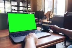 妇女使用膝上型计算机的` s手有空白的桌面屏幕的,当喝在木桌上的热的咖啡在咖啡馆时 免版税库存图片