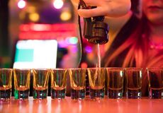 妇女侍酒者倾吐的liqour射击 免版税图库摄影