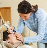 妇女供以人员的水滴洗眼 免版税图库摄影