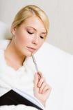 妇女保留与一支黑盖子和笔的书 免版税库存照片