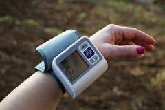 妇女保重健康的与壁炉边敲打显示器和血压 库存照片