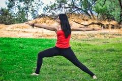 妇女信奉瑜伽者在公园执行战士姿势 免版税图库摄影