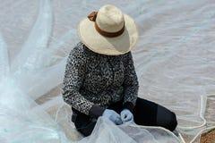 妇女修补工作捕鱼网 免版税库存照片