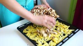 妇女倒在烘烤盘子上的切的土豆 然后他加切好的蘑菇 股票视频