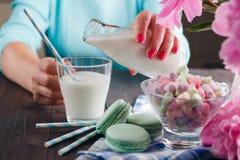 妇女倒在玻璃的牛奶 免版税库存照片