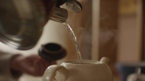 妇女倒开水入杯子和在茶包的酿造茶 妇女倾吐热水入茶壶用茶 股票录像