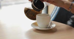 妇女倒茶入在咖啡馆的杯子 影视素材