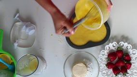 妇女倒面团入烘烤盘 在桌旁边是饼的成份 股票视频
