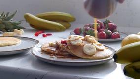 妇女倾倒在薄煎饼之上的浓缩牛奶用香蕉 影视素材