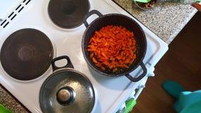 妇女倾吐它入平底深锅并且油煎被击碎的红萝卜 与一把烹饪小铲的混乱 影视素材