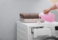 妇女倾吐的洗涤剂到在洗衣机的盖帽里户内,特写镜头 免版税库存图片