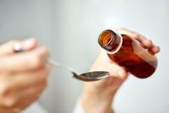 妇女倾吐的疗程从瓶到匙子 库存照片