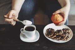 妇女倾吐的糖到吃含糖的食物的杯子里 免版税库存图片