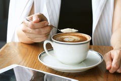 妇女倾吐的糖到咖啡杯里 使上瘾的糖 图库摄影