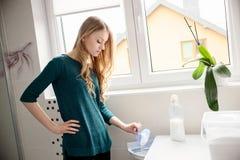 妇女倾吐的洗涤剂到洗衣机里 库存照片