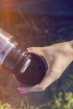 妇女倾吐从热水瓶烧瓶的水入金属杯子光泄漏样式 免版税图库摄影