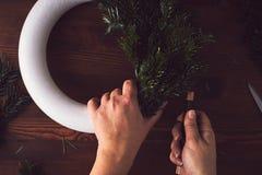 妇女做一个传统圣诞节花圈 图库摄影