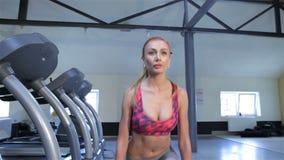 妇女做与弯曲的脚腕的步在健身中心 股票录像