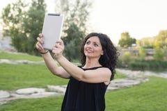 妇女做与片剂的selfie 免版税库存照片