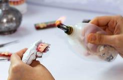 妇女做假牙的手工 免版税库存图片
