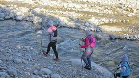 妇女做北欧走本质上在山河附近 女孩和孩子使用迁徙的棍子和北欧杆 股票录像