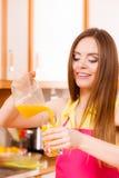 妇女做在榨汁器的橙汁加工在玻璃的倾吐的饮料 免版税图库摄影