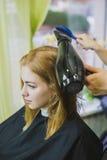 妇女做在沙龙剪的头发 图库摄影