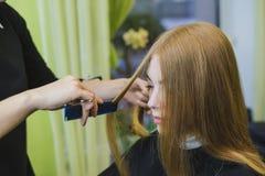 妇女做在沙龙剪的头发 库存照片