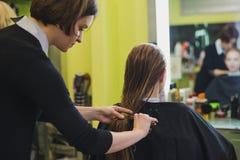 妇女做在沙龙剪的头发 库存图片