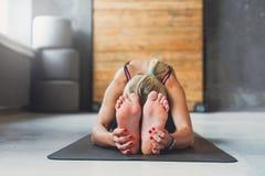 妇女做在类的瑜伽姿势,坐向前弯asana 库存图片