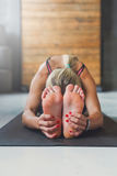 妇女做在类的瑜伽姿势,坐向前弯asana 免版税库存图片