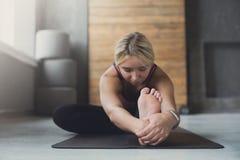 妇女做在类的瑜伽姿势,坐向前弯asana 免版税库存照片