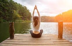 妇女做室外的瑜伽 执行女子瑜伽 免版税库存照片