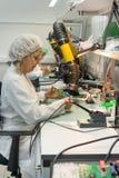 妇女做焊接无线电组分到电子委员会 电子设备的生产的植物 免版税库存照片