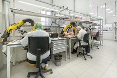 妇女做焊接无线电组分到电子委员会 电子设备的生产的植物 库存图片