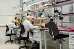 妇女做焊接无线电组分到电子委员会 电子设备的生产的植物 图库摄影