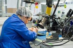 妇女做焊接无线电组分到电子委员会 电子设备的生产的植物 免版税库存图片