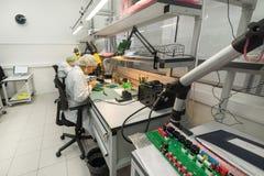 妇女做焊接无线电组分到电子委员会 电子设备的生产的植物 免版税图库摄影