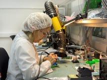 妇女做焊接无线电组分到电子委员会 电子设备的生产的植物 库存照片