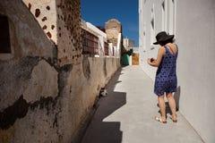 妇女做照片在街道的一只猫 免版税图库摄影